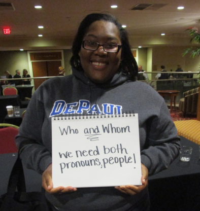 """Copy Editor, Dilane Anner, with her grammar pet peeve. The sign reads, """"who and whom we need both pronouns people."""""""
