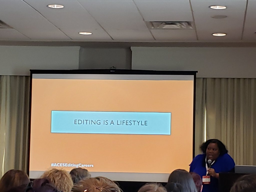 """Dilane Mitchell standing at a podium and speaking into a microphone. Behind her is a screen that says, """"Editing is a lifestyle."""""""